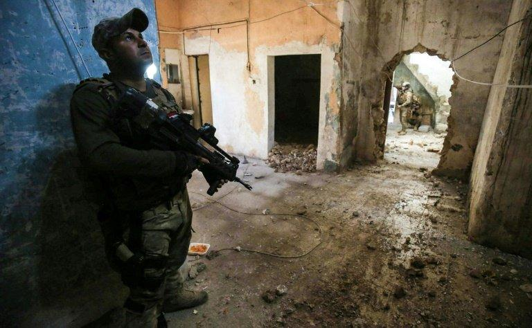 Iraqi forces advance in a house in the Old City in west Mosul on March 17, 2017