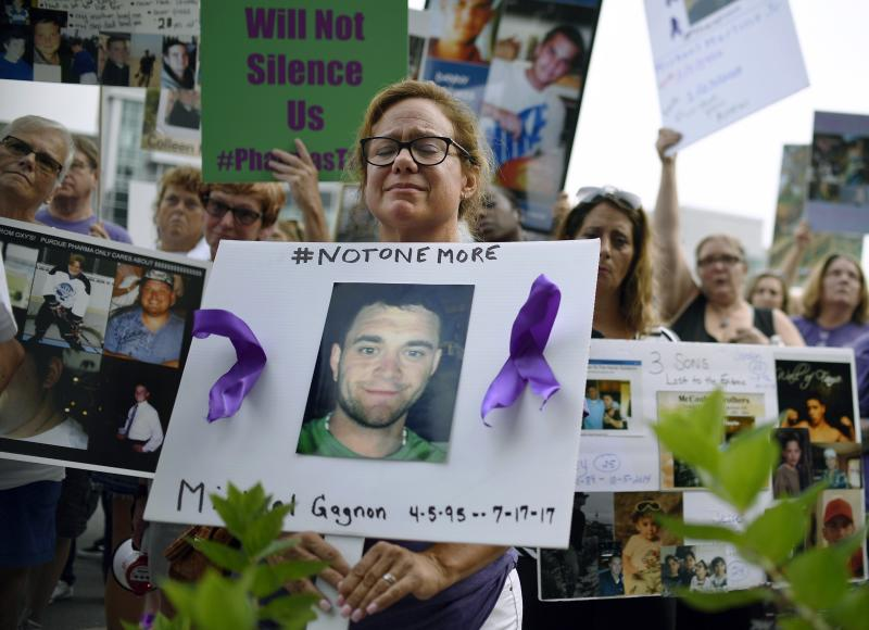 FILE - In this Friday, Aug. 17, 2018, file photo, Christine Gagnon of Southington, Conn., protests with other family and friends who have lost loved ones to OxyContin and opioid overdoses at Purdue Pharma LLP headquarters in Stamford, Conn. Gagnon lost her son Michael 13 months earlier. Reports emerging about a possible financial settlement in 2019 with Purdue Pharma, the company that has come to symbolize the nation's opioid epidemic, suggests the settlement amount won't come anywhere near what the national crisis has cost. (AP Photo/Jessica Hill, File)