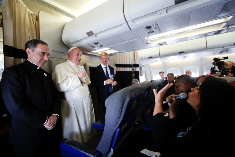 Pope Francis (2ndL) is flanked by his spokesperson Matteo Bruni (3rdL) and the Pope's trip organizer Father Mauricio Rueda, during his flight from Antamanarivo to Rome, on September 10, 2019, after his seven-day pastoral trip to countries in Africa