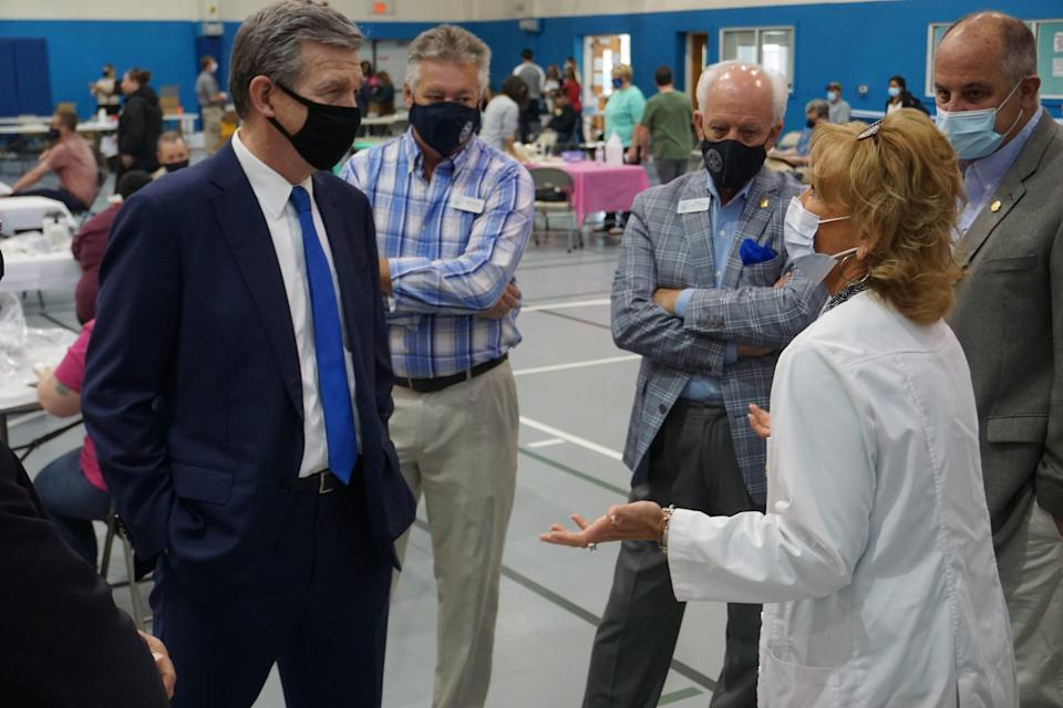 Dare County Public Health Nursing Director Debbie Dutton speaks to Governor Roy Cooper as Dare County commissioners Steve House, Chairman Bob Woodard and Jim Tobin listen.