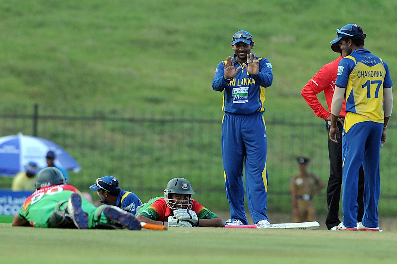 Sri Lankan cricketer Tillakaratne Dilshan (C) teases Bangladeshi batsmen Mahmudullah and Tamim Iqbal as they lie on the ground after wasps invaded the field during the opening one-day international (ODI) match between Sri Lanka and Bangladesh at The Suriyawewa Mahinda Rajapakse International Cricket Stadium in the southern district of Hambantota on March 23, 2013. Sri Lankan cricket captain Angelo Mathews won the toss and elected to field. AFP PHOTO/ Ishara S. KODIKARA (Photo credit should read Ishara S.KODIKARA/AFP/Getty Images)