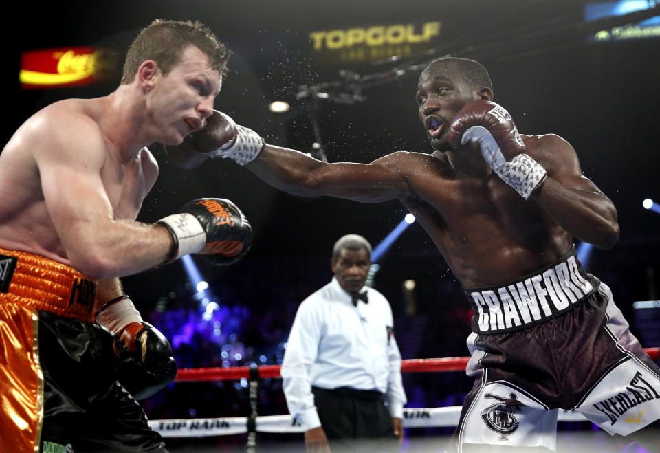 Terence Crawford, right, lands a punch on Jeff Horn, of Australia, in a welterweight title boxing match, Saturday, June 9, 2018, in Las Vegas. (AP Photo)