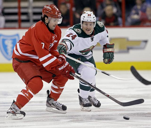 Carolina Hurricanes' Ryan Murphy (7) and Minnesota Wild's Matt Cooke (24) chase the puck during the first period of an NHL hockey game in Raleigh, N.C., Saturday, Nov. 9, 2013. (AP Photo/Gerry Broome)