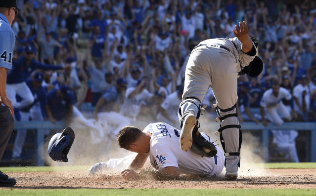 Los Angeles Dodgers' Corey Seager, bottom center, scores the winning run on a walkoff double by Max Muncy as San Diego Padres catcher Francisco Mejia, top center, makes a late tag during the ninth inning of a baseball game Sunday, Aug. 4, 2019, in Los Angeles. (AP Photo/Mark J. Terrill)