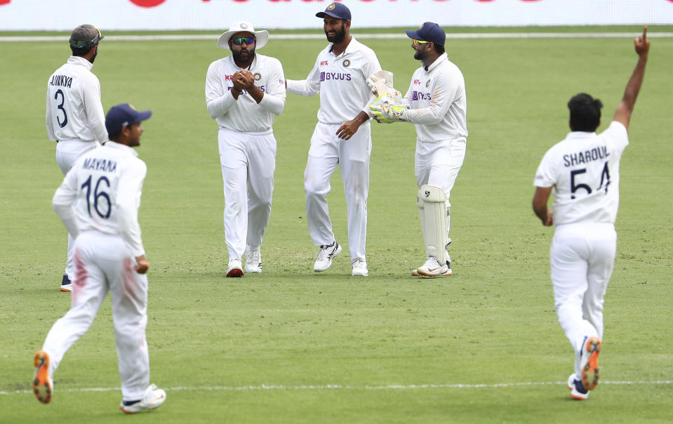 India's Rohit Sharma, second left, reacts as he takes a catch to dismiss Australia's Cameron Green during play on day four of the fourth cricket test between India and Australia at the Gabba, Brisbane, Australia, Monday, Jan. 18, 2021. (AP Photo/Tertius Pickard)