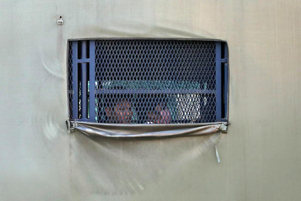 <p>Myanmar migrants to be deported from Malaysia are seen inside an immigration truck, in Lumut, Malaysia on 23 February, 2021</p> (Reuters)