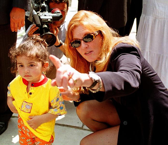 """FILE In this Thursday, June 11, 1998 file photo Britain's Duchess of York Sarah Ferguson points at the cameras as she kneels beside a Turkish child during her visit to the Blue Mosque in Istanbul. A Turkish court has begun a trial Friday May 4, 2012 against Britain's Duchess of York for allegedly taking part in the secret filming of two orphanages in Turkey, the state-run news agency said. Sarah Ferguson, who is being tried in absentia, faces charges of going """"against the law in acquiring footage and violating privacy"""" of five children at one of the orphanages, the Anadolu Agency said. If convicted, she could receive a maximum sentence of 22 1/2 years in prison. (AP Photo/Murad Sezer, File)"""