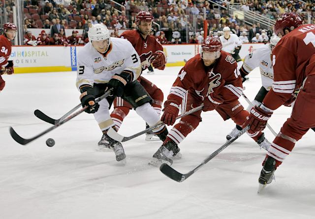 Anaheim Ducks' Jakob Silfverberg (33) and Phoenix Coyotes' Jeff Halpern (14) reach for the puck during the first period of an NHL hockey game, Saturday, Jan. 11, 2014, in Glendale, Ariz. (AP Photo/Matt York)