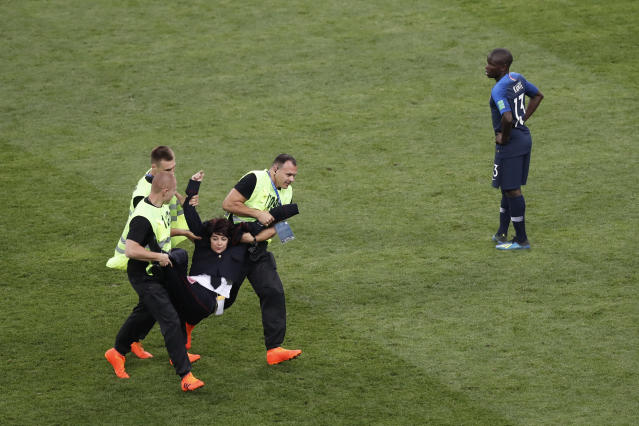 France's Ngolo Kante watches as a woman is dragged away by stewards after running into the pitch during the final match between France and Croatia at the 2018 soccer World Cup in the Luzhniki Stadium in Moscow, Russia, Sunday, July 15, 2018. (AP Photo/Rebecca Blackwell)