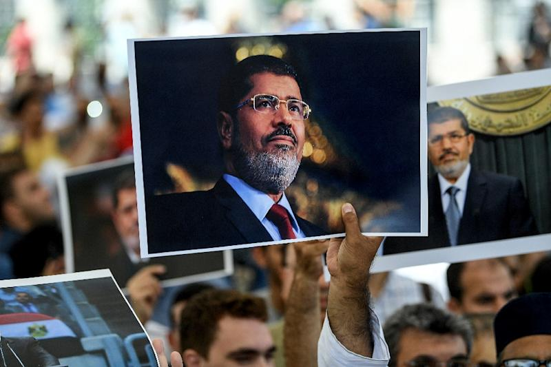 People hold picture of Egyptian President Mohamed Morsi during a symbolic funeral cerenomy on June 18, 2019 at Fatih mosque in Istanbul (AFP Photo/)