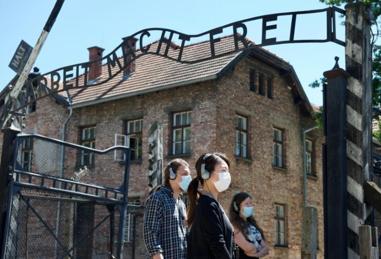 "As the site reopens following Coronavirus lockdown, visitors to Auschwitz contemplate the entrance gate with its inscription ""Work sets you free"""