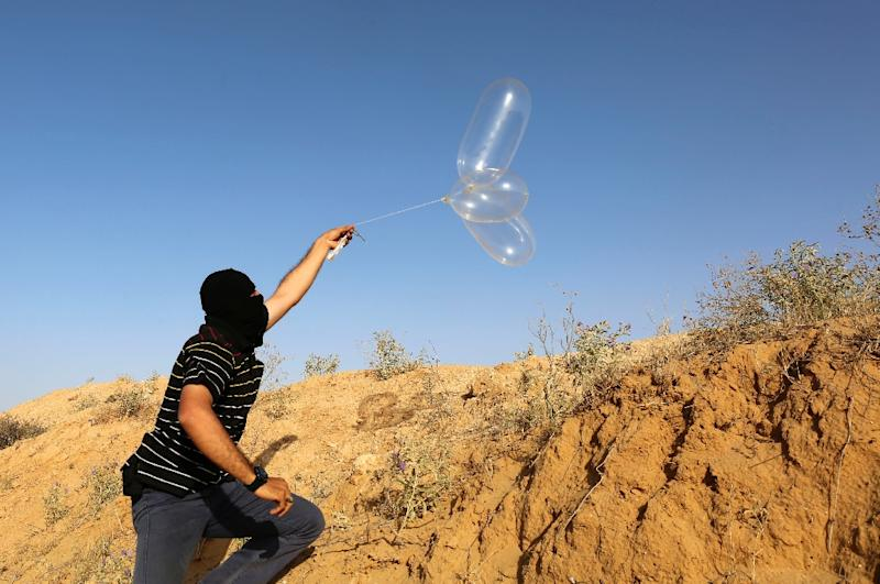 A masked Palestinian launches a balloon loaded with flammable materials to be flown toward Israel at the Israel Gaza border in Rafah in the southern Gaza Strip