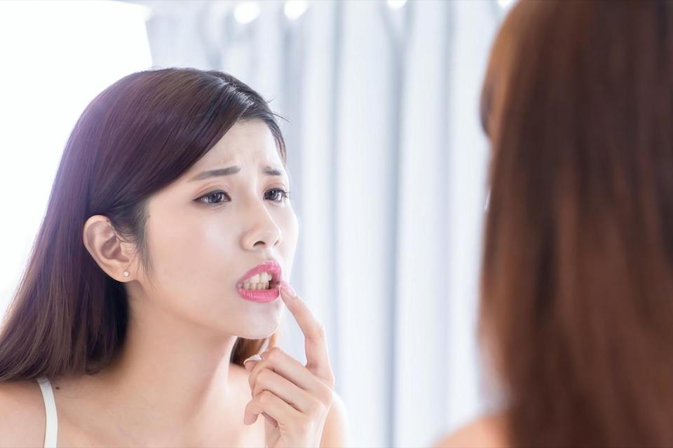 woman worry about her teeth and look in the mirror.