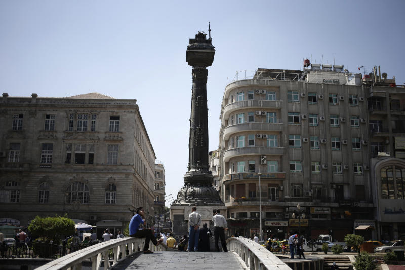 FILE - In this Sunday, Aug. 25, 2013 file photo, Syrians gather in the Marjeh square, in Damascus, Syria. The veneer of normalcy is thin in Damascus, the stronghold of President Bashar Assad's rule, after more than 2 1/2 years of bloodshed. (AP Photo/Hassan Ammar)