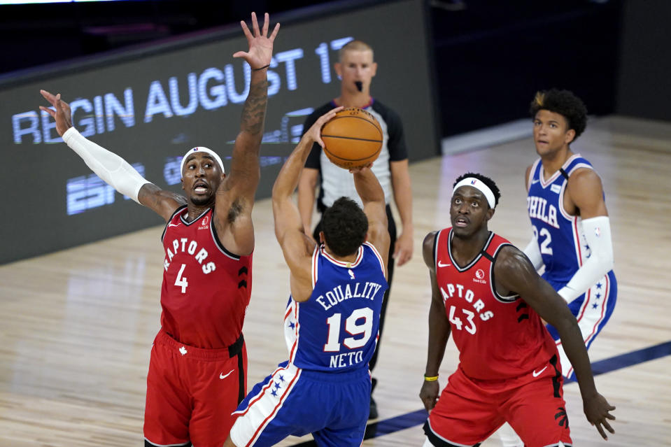 Philadelphia 76ers' Raul Neto (19) shoots a basket against Toronto Raptors' Rondae Hollis-Jefferson (4) and Pascal Siakam (43) during the first half of an NBA basketball game Wednesday, Aug. 12, 2020 in Lake Buena Vista, Fla. (AP Photo/Ashley Landis, Pool)