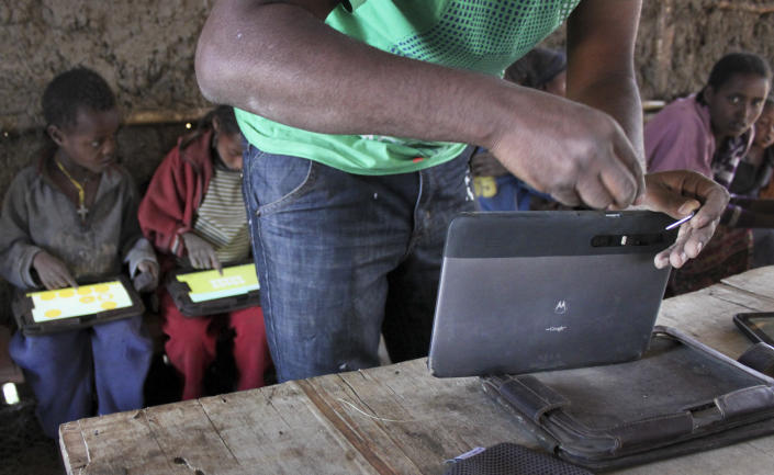 In this photo taken Tuesday, Nov. 27, 2012, technician Michael Girma, from the One Laptop Per Child project, switches out the memory card from a tablet computer given to children in the village of Wenchi, Ethiopia. The project gave tablets to the children in the poor, illiterate village to see how much the children could teach themselves and now many kids can recite the English alphabet and spell words in English. (AP Photo/Jason Straziuso)