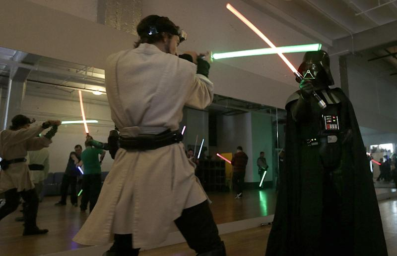 Golden Gate Knights instructor Alain Block, left, and Gary Ripper, dressed as Darth Vader, demonstrate light saber moves during class in San Francisco, Sunday, Feb. 10, 2013. A group of San Francisco Star Wars fans who want to travel to a galaxy not that far away have created a combat choreography class for Jedis-in-training with their weapon of choice: the light saber. (AP Photo/Jeff Chiu)