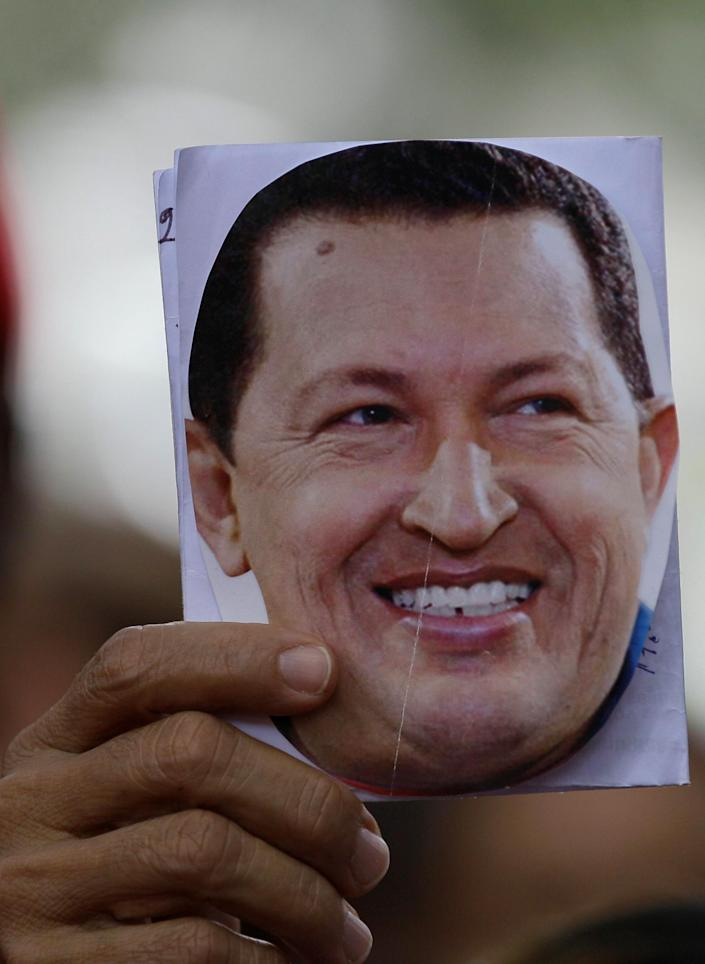 """A person holds up an image of Venezuela's President Hugo Chavez during a demonstration in support of him at the Simon Bolivar square in Caracas, Venezuela, Sunday Dec. 9, 2012. Chavez was heading back to Cuba on Sunday for more cancer surgery after announcing that the illness returned despite two previous operations, chemotherapy and radiation treatment. Chavez said Saturday that if there are """"circumstances that prevent me from exercising the presidency further"""" Vice-President Nicolas Maduro should replace him for the remainder of his term. (AP Photo/Fernando Llano)"""