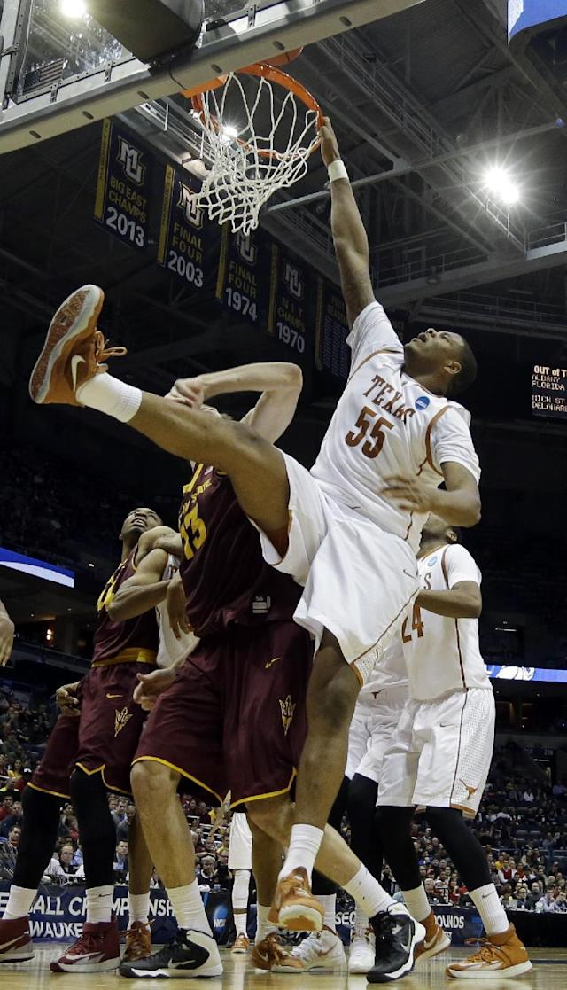 Texas center Cameron Ridley (55) grabs on to the rim as he misses a dunk against Arizona State center Jordan Bachynski (13) during the second half of a second-round game in the NCAA college basketball tournament Thursday, March 20, 2014, in Milwaukee. (AP Photo/Morry Gash)