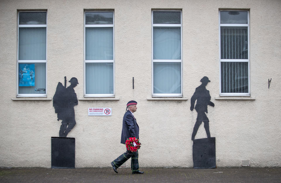 Veteran Charlie MacVicar, who served for 23 years with the Royal Scots (Edinburgh Unit), walks past the Royal British Legion on his way to lay a wreath at the Remembrance Garden on Remembrance Sunday, in Grangemouth, Scotland, Sunday, Nov. 8, 2020. (Jane Barlow/PA via AP)