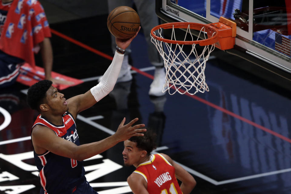 Washington Wizards forward Rui Hachimura (8) lays in a basket over Atlanta Hawks guard Trae Young (11) during the first half of an NBA basketball game Wednesday, May 12, 2021, in Atlanta. (AP Photo/Butch Dill)