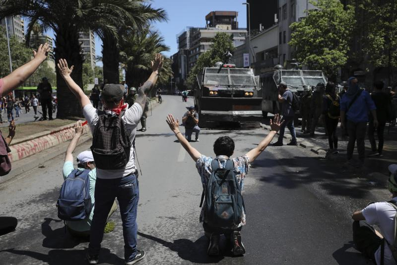 An anti-government protesters face police in Santiago, Chile, Tuesday, Oct. 22, 2019. The government said Tuesday that 15 people have died in five days of rioting, arson and violent clashes that were sparked by a hike in subway fares and have almost paralyzed the country. (AP Photo/Rodrigo Abd)