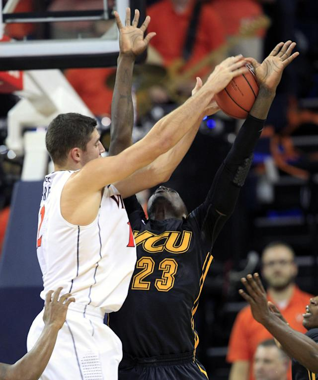 Virginia guard Joe Harris (12) grabs a rebound in front of Virginia Commonwealth forward Jarred Guest (23) during the first half of an NCAA college basketball game in Charlottesville, Va., Tuesday, Nov. 12, 2013. (AP Photo/Steve Helber)