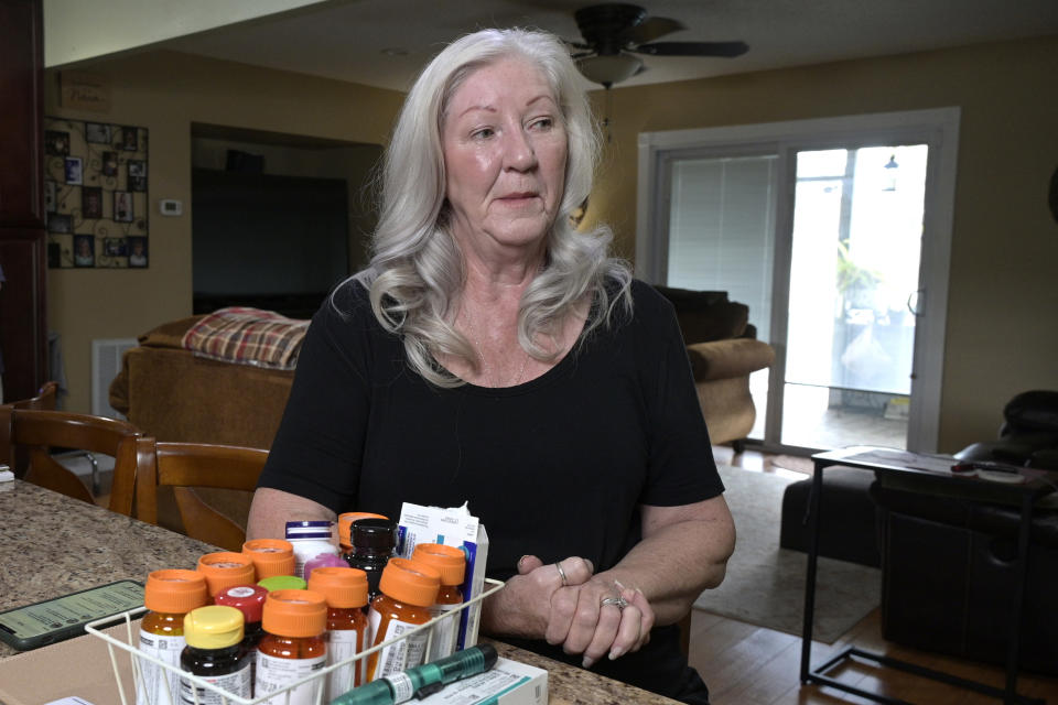 Retiree Donna Weiner, right, sits at the kitchen table with the daily prescription medications that she needs and pays over $6,000 a year through a Medicare prescription drug plan at her home, Tuesday, Oct. 5, 2021, in Longwood, Fla. Weiner supports giving Medicare authority to negotiate drug prices. Negotiating Medicare drug prices is the linchpin of President Joe Biden's ambitious health care agenda. Not only would consumers see lower costs, but savings would be plowed into other priorities such as dental coverage for retirees and lower premiums for people with plans under the Obama-era health law. (AP Photo/Phelan M. Ebenhack)