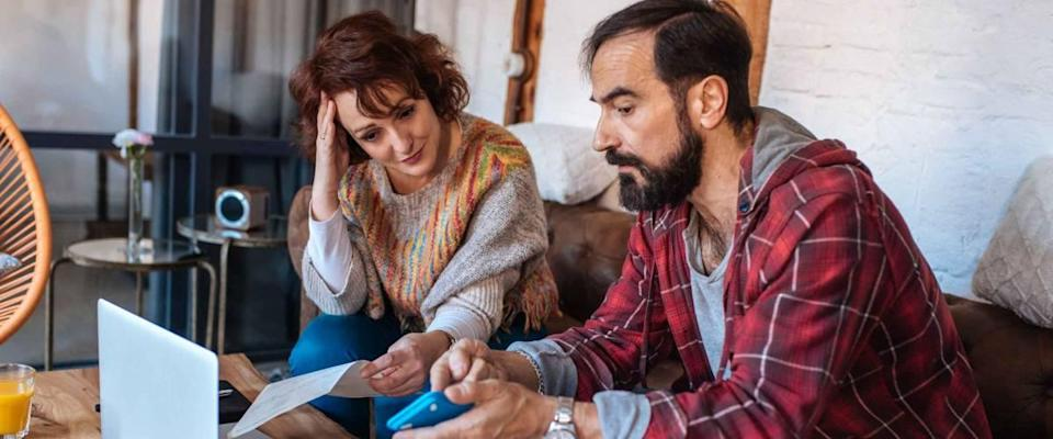 Couple sitting on the sofa at home, looking at their financial statements, stressed.