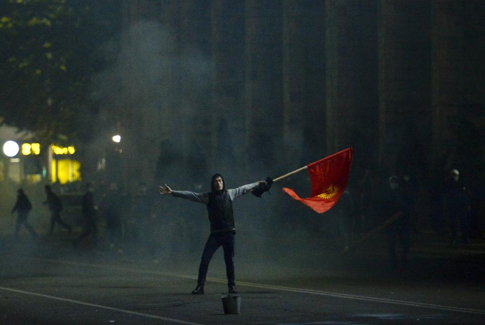 Protester waves a Kyrgyz flag during a rally against the results of a parliamentary vote in Bishkek, Kyrgyzstan, Monday, Oct. 5, 2020. Large crowds of people have gathered in the center of Kyrgyzstan's capital to protest against the results of a parliamentary election, early results of which gave the majority of seats to two parties with ties to the ruling elites amid allegations of vote buying. (AP Photo/Vladimir Voronin)