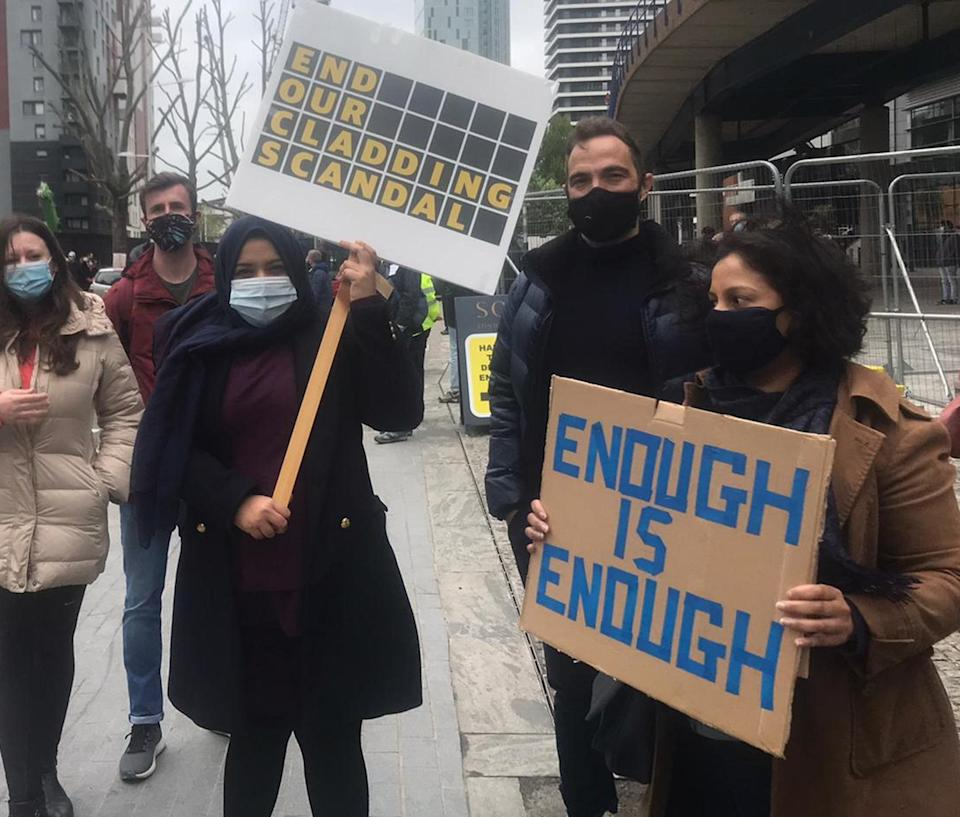 Signs held by protesters, which read 'END OUR CLADDING SCANDAL' and 'ENOUGH IS ENOUGH' - A woman with her head covered, wearing a light blue mask, holds a sign with yellow writing on a black background. To her right, a woman wearing a black mask and a brown coat holds a cardboard sign with blue lettering