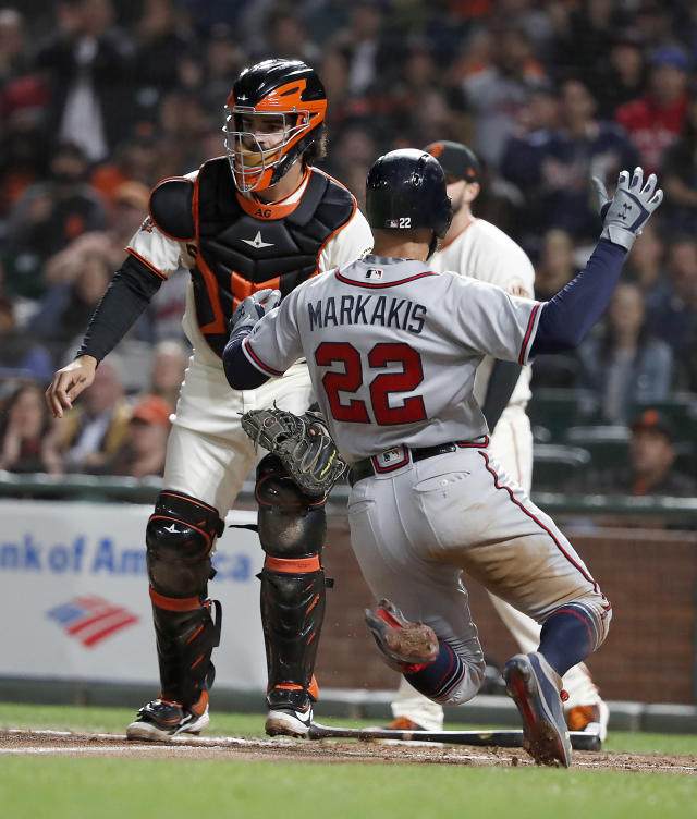 Atlanta Braves' Nick Markakis (22) slides into home plate past San Francisco Giants catcher Aramis Garcia, left, on a sacrifice fly Ender Inciarte during the fourth inning of a baseball game in San Francisco, Tuesday, Sept. 11, 2018. (AP Photo/Tony Avelar)
