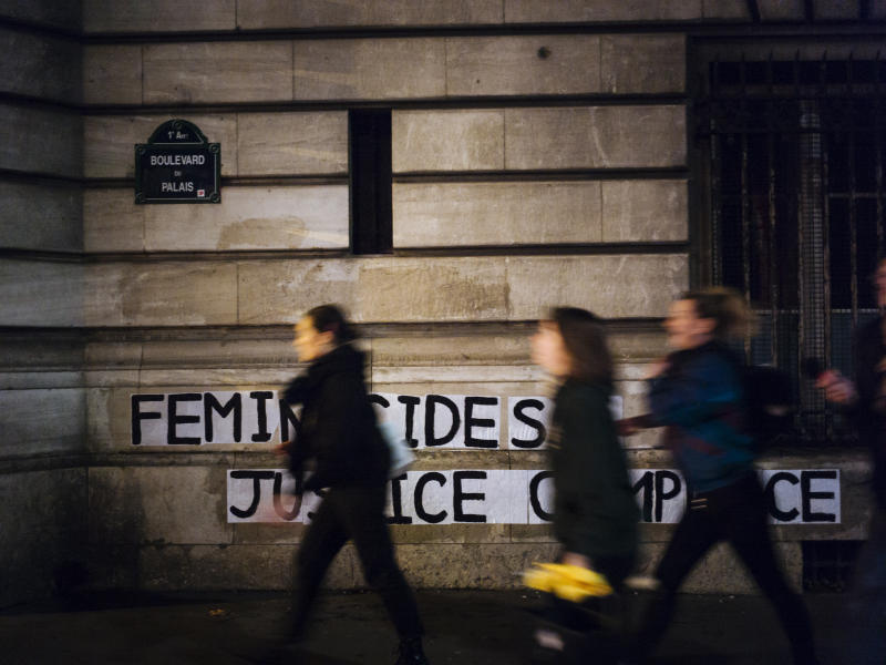 "In this Nov. 4 2019 photo, Lea, Pauline and Clivia, from left, walk past a slogan they recently pasted on walls of the Palais de Justice courthouse reading "" Femicides : guilty state, accomplice justice"" in Paris. (AP Photo/Kamil Zihnioglu)"