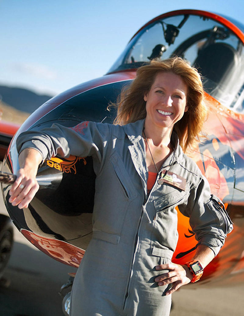 """This photo provided by the National Championship Air Races shows Heather Penney in front of the race jet """"Ragu Grace"""", in Reno, Nev.. Fighter pilot Heather """"Lucky"""" Penney didn't have time to be scared. There was a hijacked commercial airliner headed to Washington, D.C., and she was ordered to stop it. On Sept. 11, 2001, Penney and her commanding officer were ordered to stop United Airlines Flight 93 from hitting a target in the nation's capital. But they didn't have any missiles or even ammunition. So Col. Marc Sasseville decided they would use their own planes to bring it down.  (AP Photo/National Championship Air Races, Tyson Rininger)"""