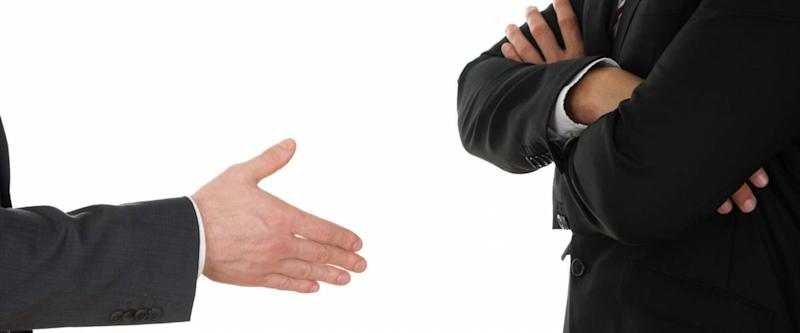 Person Offering Handshake To Businessman With Arm Crossed Over White Background
