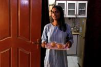 Nisha Rao, 28, a transgender woman who became country's first practicing lawyer, serves tea to her guests at home in Karachi