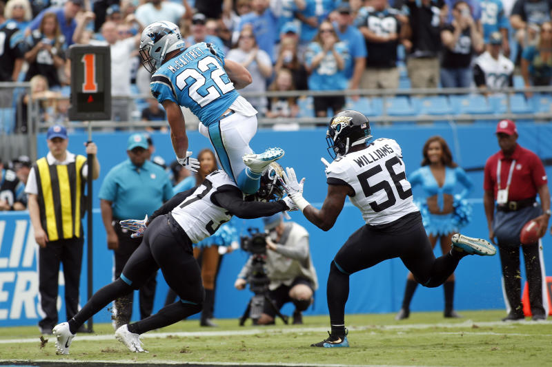 Carolina Panthers running back Christian McCaffrey (22) jumps over Jacksonville Jaguars cornerback Tre Herndon (37) as linebacker Quincy Williams (56) looks to tackle during the first half of an NFL football game in Charlotte, N.C., Sunday, Oct. 6, 2019. McCaffrey scored a touchdown on the play. (AP Photo/Brian Blanco)