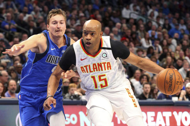 FILE - In this Feb. 1, 2020, file photo, Atlanta Hawks guard Vince Carter (15) drives to the basket against Dallas Mavericks guard Ryan Broekhoff (45) during the second half of an NBA basketball game in Dallas. Carter made his retirement official Thursday, June 25, 2020, announcing on his podcast that his 22-year NBA career has come to an end. The announcement was largely a formality, since the 43-year-old Carter had said many times over the course of this season that this would be his last in the NBA. His 22 seasons are the most in league history, and he became the first NBA player to appear in four different decades. (AP Photo/Richard W. Rodriguez, File)