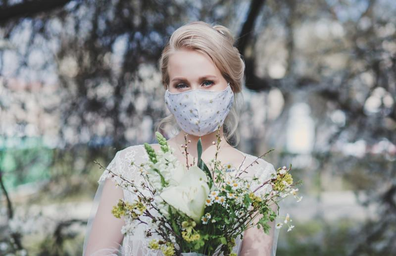 beautiful bride with a bouquet in a protective mask on the background of flowering trees. spring