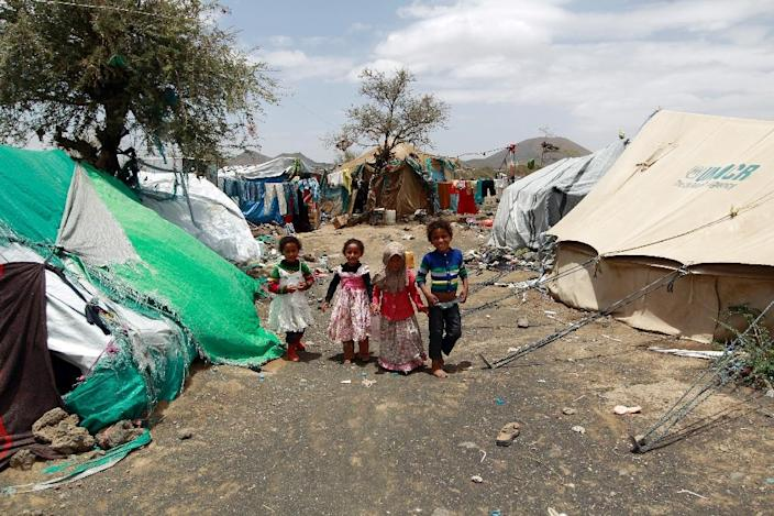 Yemeni children walk past tents at a makeshift camp housing Internally Displaced Persons (IDPs) who fled their homes due to the ongoing conflict between loyalist forces and Huthi rebels, on April 16, 2016 on the outskirts of the governorate of Sanaa (AFP Photo/Mohammed Huwais)
