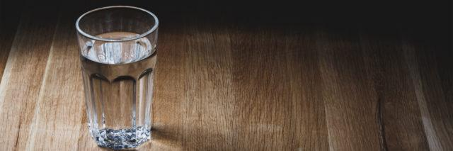 Glass of water on wood table surface.