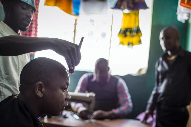 <p>A barber works with precision at a shop in Maramba, a township of Livingstone, Zambia. </p>