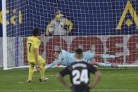 Villareal's Gerard Moreno, left, scores the penalty kick past Real Madrid's goalkeeper Thibaut Courtois as Real Madrid's Mariano Diaz looks on during the Spanish La Liga soccer match between Villarreal and Real Madrid in Ceramica stadium in Villarreal, Spain, Saturday Nov. 21, 2020. (AP Photo/Alberto Saiz)