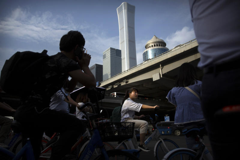 """People wait cross the street in a crosswalk in the central business district in Beijing, Friday, May 24, 2019. Stepping up a propaganda offensive against Washington, China's state media on Friday accused the U.S. of seeking to """"colonize global business"""" by targeting telecom equipment giant Huawei and other Chinese companies. (AP Photo/Mark Schiefelbein)"""