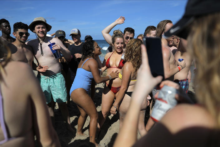 Students in bathing suits and no face masks are tightly packed on a beach