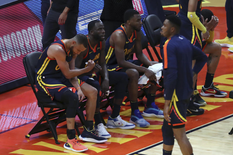 Golden State Warriors' Stephen Curry, left, Draymond Green, center and Andrew Wiggins sit during a timeout in overtime of an NBA basketball Western Conference play-in game against the Memphis Grizzlies in San Francisco, Friday, May 21, 2021. (AP Photo/Jed Jacobsohn)