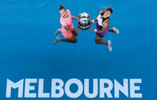 Elise Mertens and Aryna Sabalenka leap into the air after winning the women's doubles title
