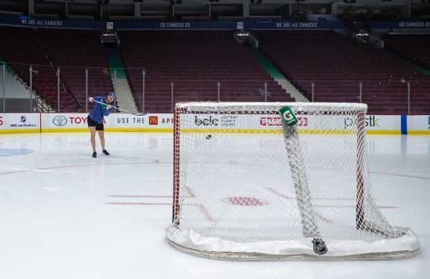 Vancouver Canucks goalie Thatcher Demko shoots a puck after the team's game against the Calgary Flames was postponed due to an outbreak of COVID-19 on March 31.