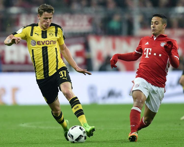 Dortmund's Erik Durm (left) and Bayern Munich's Thiago Alcantara in action during the German Cup semi-final match in Munich, on April 26, 2017
