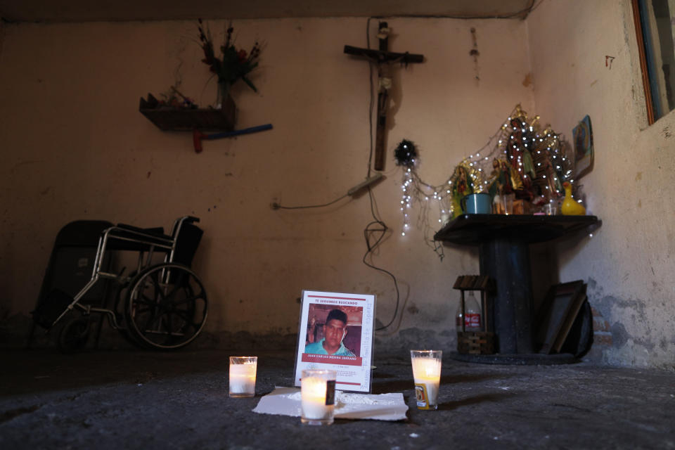 FILE - This Feb. 13, 2020 file photo shows a memorial for Juan Carlos Medina Serrano in his family's living room, the day his remains were buried, in Irapuato, Guanajuato state, Mexico. Armed men took the 32-year-old from his house on Dec. 3, 2019, and a few days later, authorities found 19 rotting bodies buried in a backyard in a nearby town, but it took two months for them to notify his wife that her husband was one of the bodies. The two most powerful drug cartels in the hemisphere are battling over this industrial and farming hub of central Mexico — a state that has attracted gangs for the same reason it has lured auto manufacturers: road and rail networks that lead straight to the U.S. border. (AP Photo/Rebecca Blackwell, File)